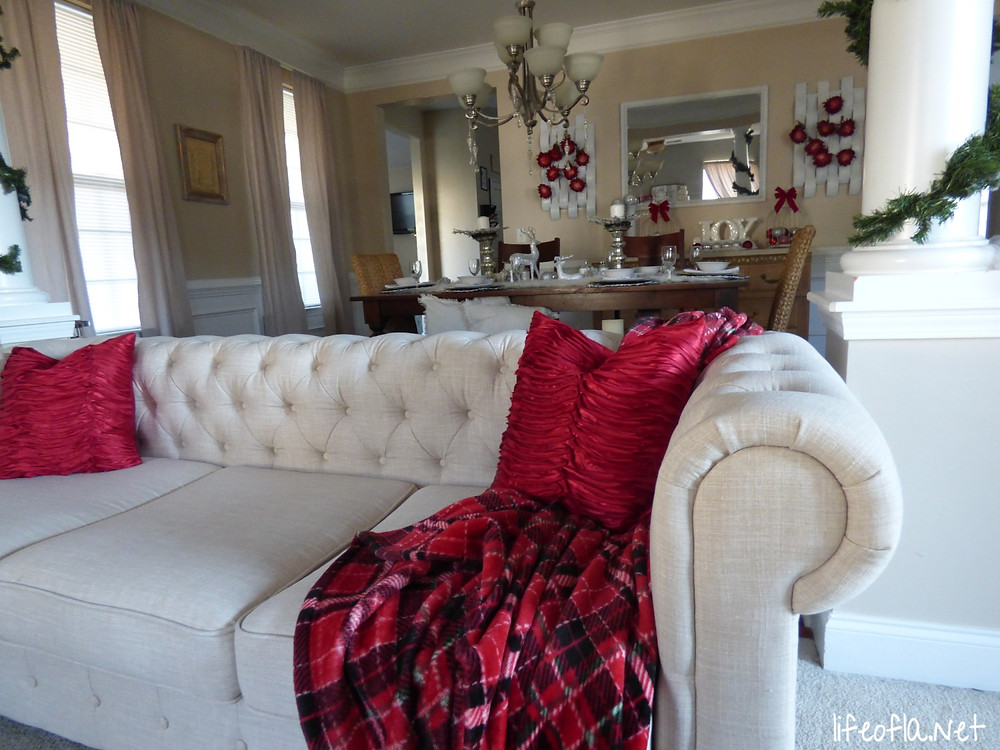 Chesterfield sofa with red pillows & buffalo check throw