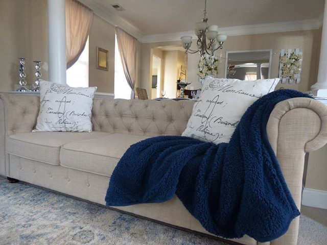 Cozy beige chesterfield sofa with navy throw