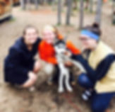 3 Girls smile while holding Lakota as a puppy