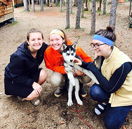 3 Girls smile while holding Lakota as a puppy