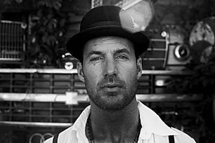 black and white portrait photo of a man wearing a fedora hat