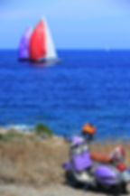 Purple scooter parked on a cliff near the ocean with sailboats in background