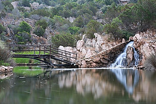 outdoor park with a bridge and waterfall flowing into a pond, in Sardinia Italy