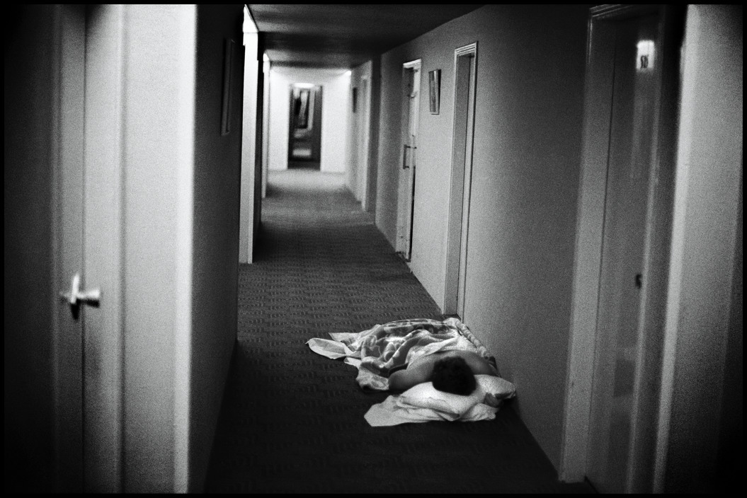 Hotel guests sleep in the hallway of