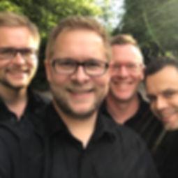 Die Musiker der Hochzeitsband und Partyband Groove Project posieren nebeneinander stehend vor der Kamera.