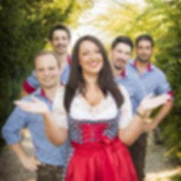 Die Musiker der Hochzeitsband und Partyband Voglwuid auf einen Kiesweg hintereinander stehend.