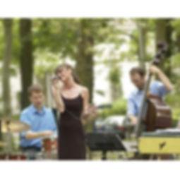Die Musiker der Hochzeitsband Cotton Club auf einer Hochzeit spielen Musik im Freien bei Kaffee und Kuchen.