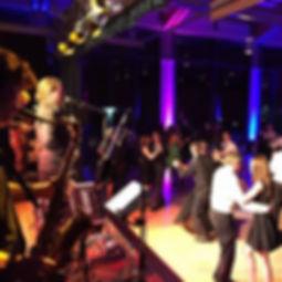 Die Musiker der Hochzeitsband und Partyband Ensemble Taktlos spielen Musik auf der Bühne mit tanzenden Paaren vor der Bühne.