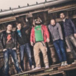 Die Musiker der Hochzeitsband und Partyband Jive nebeneinanderunte einem Holzdach stehend.