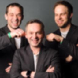 Die Musiker der Hochzeitsband und Partyband d`Zechpreller ziehen dem Frontmann vor einer Photowand an den Ohren.