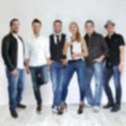 Die Musiker der Hochzeitsband und Partyband Edelwuid posieren in einer Reihe vor einer Wand.