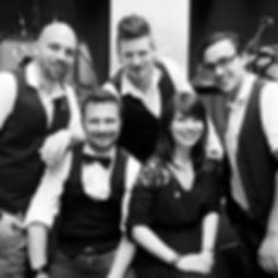 Die Musiker der Hochzeitsband und Partyband Hautnah au einer Hochzeit stehend vor der Bühne und ihren Instrumenten.