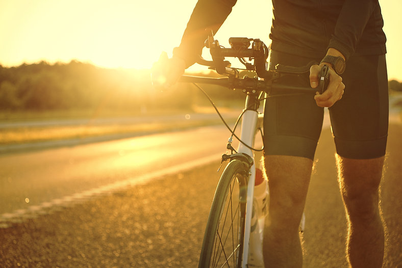 man-holding-bicycle-on-empty-sunset-road