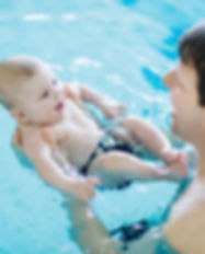 Happy middle-aged father swimming with c