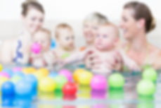 Moms and children at infant swimming les