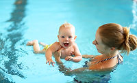 healthy family mother teaching baby swim