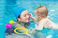 Happy mother teaches a child to swim by