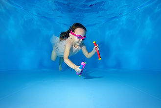 Little girl swims underwater and picking
