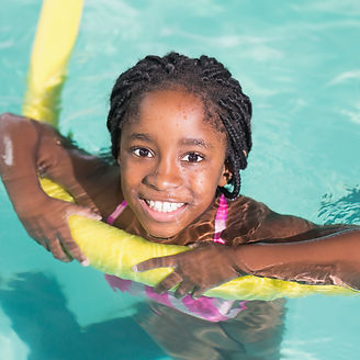 Cute little girl swimming in the pool at