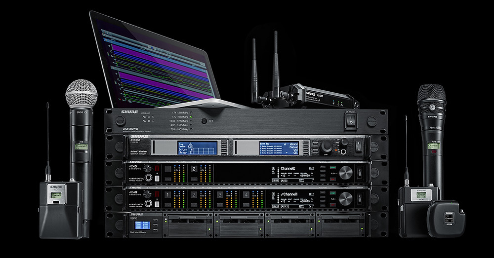 Photo of a variety of Shure Axient Digital Wireless Audio System components, including wireless microphones and rack-mount wireless receivers