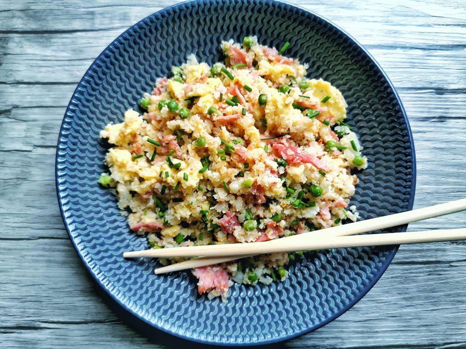 Chou fleur cantonais, jambon oeufs, petits pois dans assiette avec baguettes