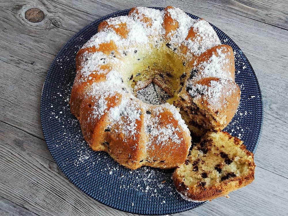 coupe du gâteau de Savoie, pépites chocolat, sucre glace, assiette bleue