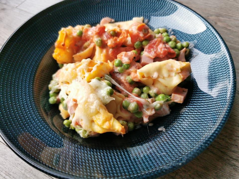 Gratin de tortellinis, jambon, petits poid, fromage dans l'ultra pro Tupperware, assiette bleue