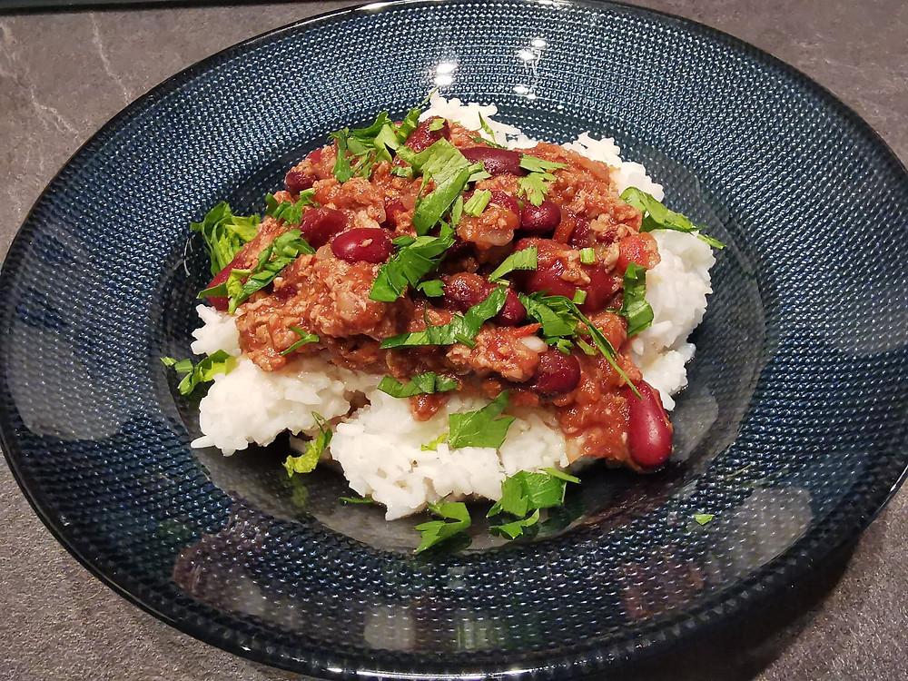 Chili con carne, riz et haricots rouge, persil, assiette bleue, sauce tomate