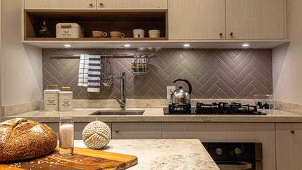 """Backsplash: é como se chama o revestimento da parede entre o balcão da cozinha e os armários superiores. Nesse caso o backsplash é um revestimento retangular, instalado em """"espinha de peixe""""."""