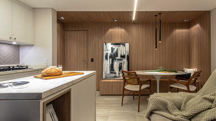 O charme da sala está no painel de madeira que envolve a área de jantar, cobrindo as paredes e também o forro.