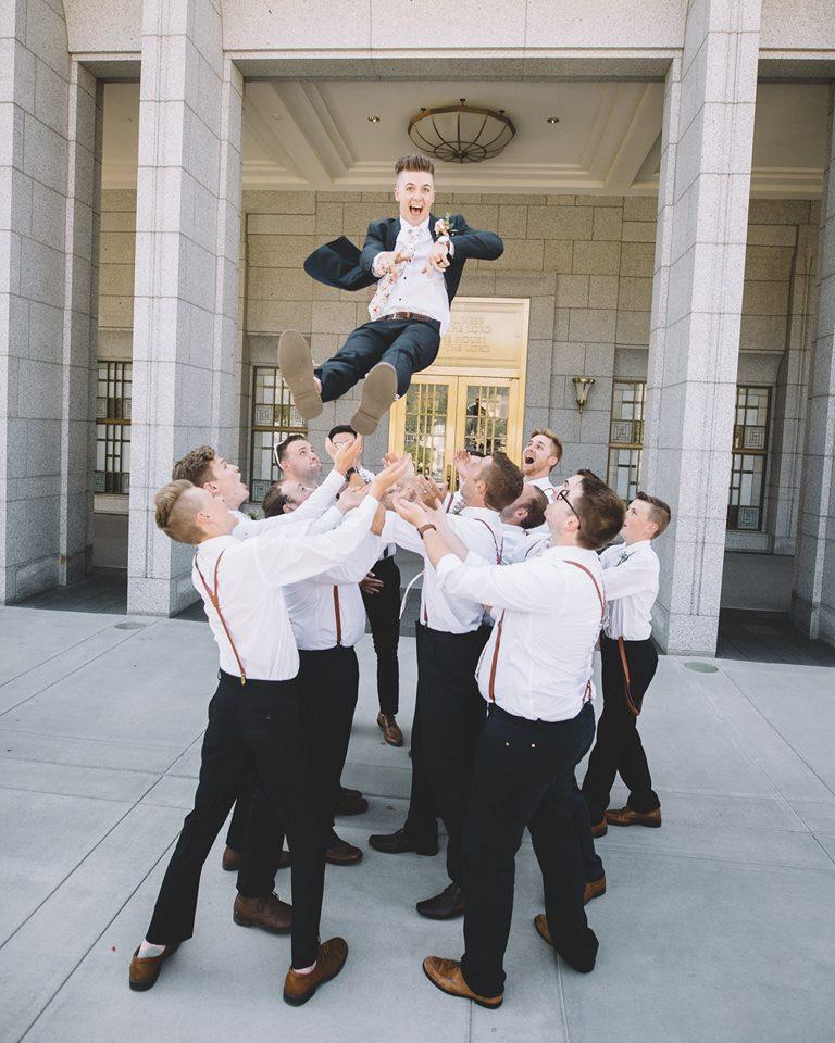 Happy Groomsmen Throwing Groom