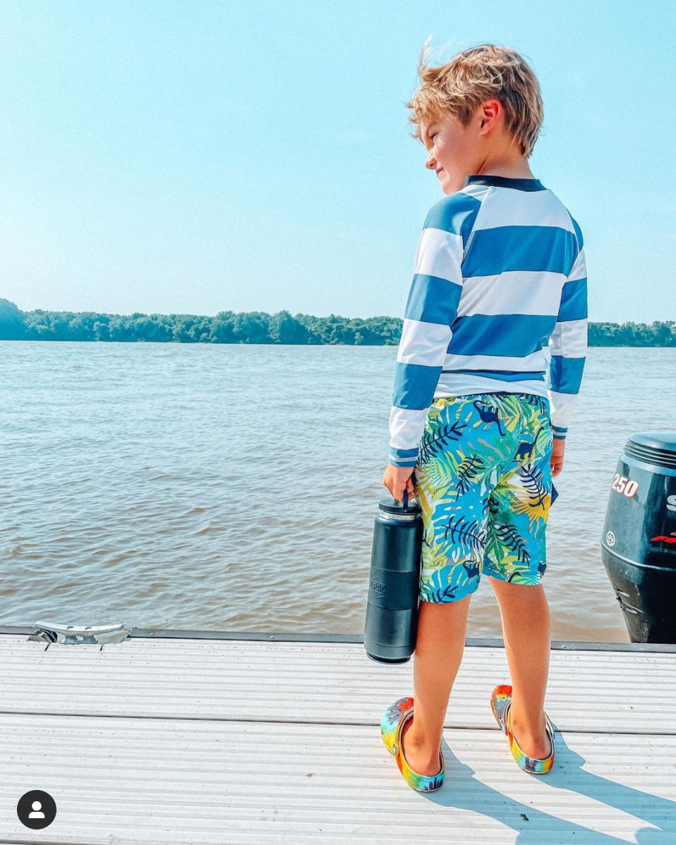 boy standing by a lake wearing striped shirt holding a black water bottle