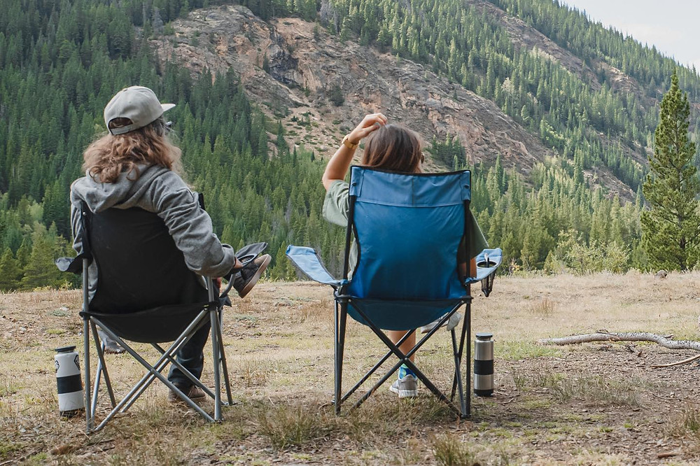 couple sitting in camping chairs looking out at a mountain campsite