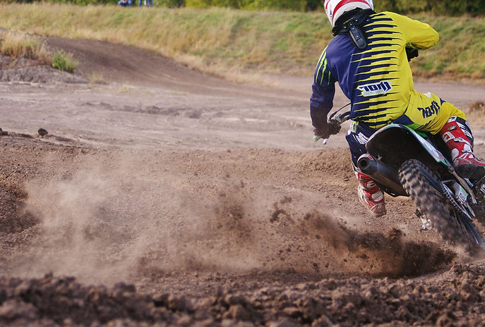 dirtbike rider wearing blue and yellow thor gear turning a corner on a motocross track