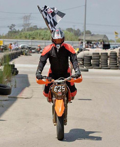 אופנוען מרים גלגל אחורי באוויר על אופנוע כתום ודגל שחמט תקוע בחליפה