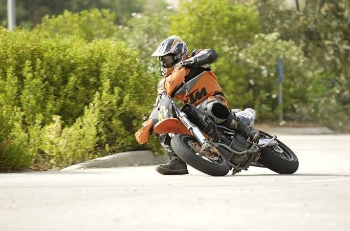 אופנוע בהשכבה עד הרגליות ורוכב עם חליפה כתומה ממותגת KTM, שיחים ברקע