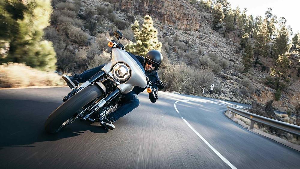 רוכב על אופנוע קסטום בכביש מתעקל, ברקע הר ועצים