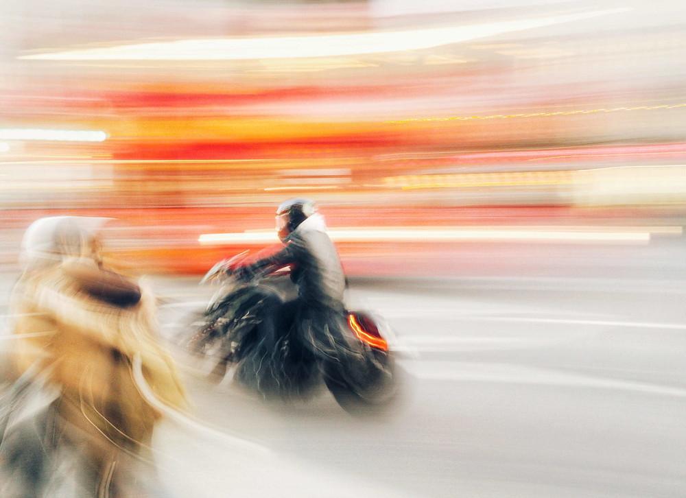 תמונה מטושטשת של אופנוע נוסע ואורות מרוחים ברקע
