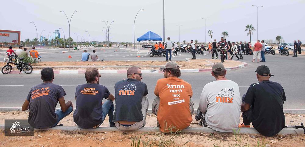 צוות מדריכים יושבים על המדרכה במגרש אימונים