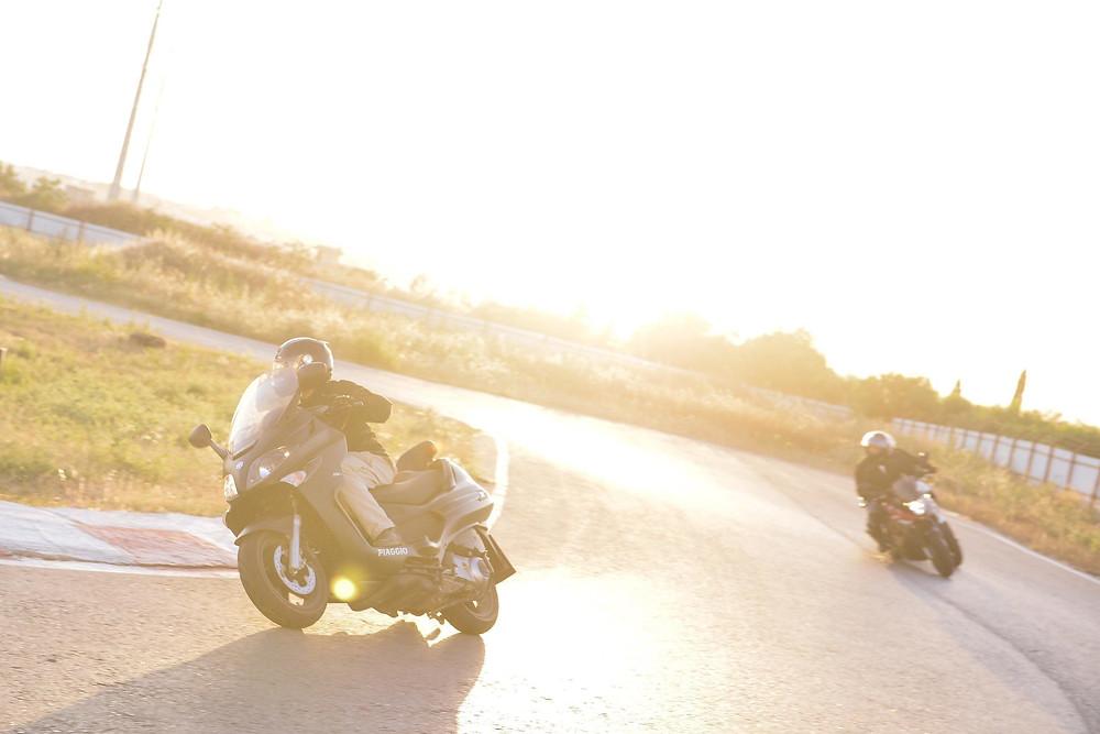 אופנועים נוסעים בפניה ימנית במסלול מירוצים, שמש נמוכה משתקפת מהאספלט