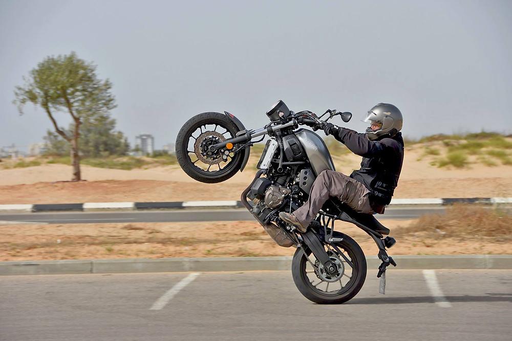 אופנוע ימאהה אפור, ווילי, רקע חולות וכביש, עץ