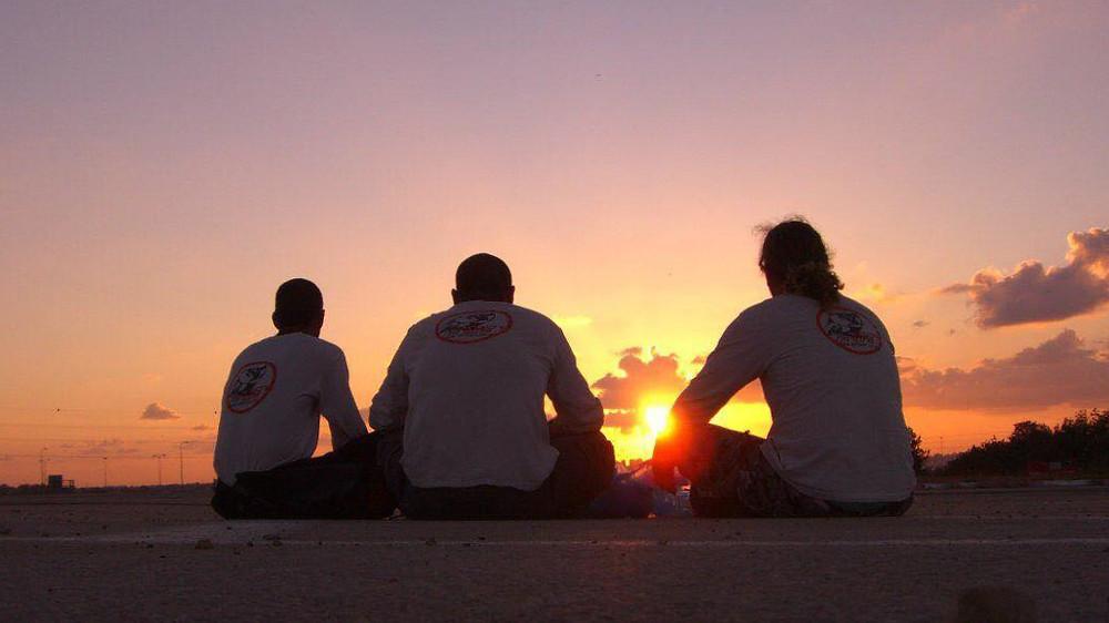 שלושה אנשים יושבים על אספלט מסתכלים על שקיעה
