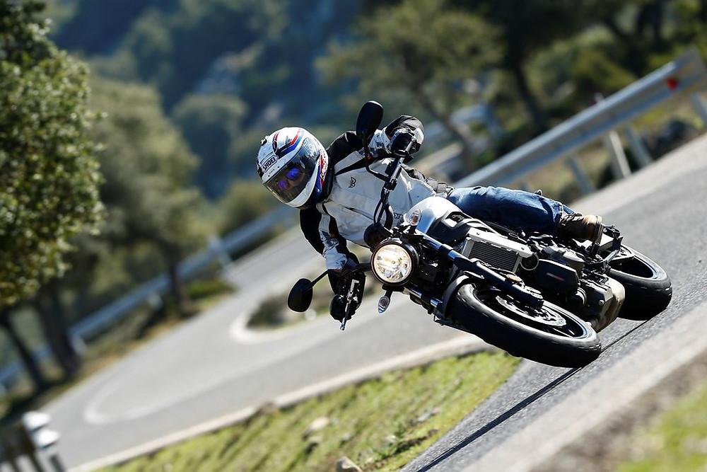 צילום בזוית של אופנוע בהטיה בכביש מפותל.