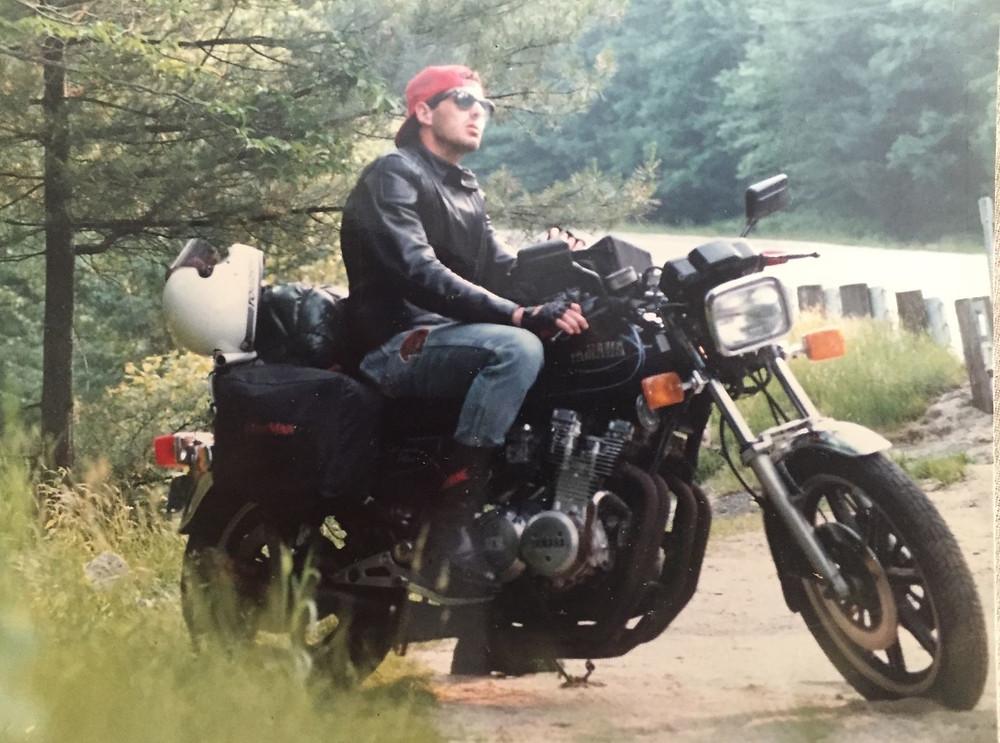 אדם יושב על אופנוע בצד הדרך בין עצים, לובש כובע אדום הפוך ומשקפי שמש