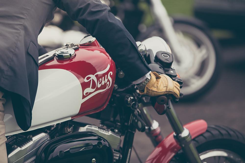 תמונת תקריב של אופנוע DEWS, אדם מחזיק בכידוןן, כפפת עור חומה