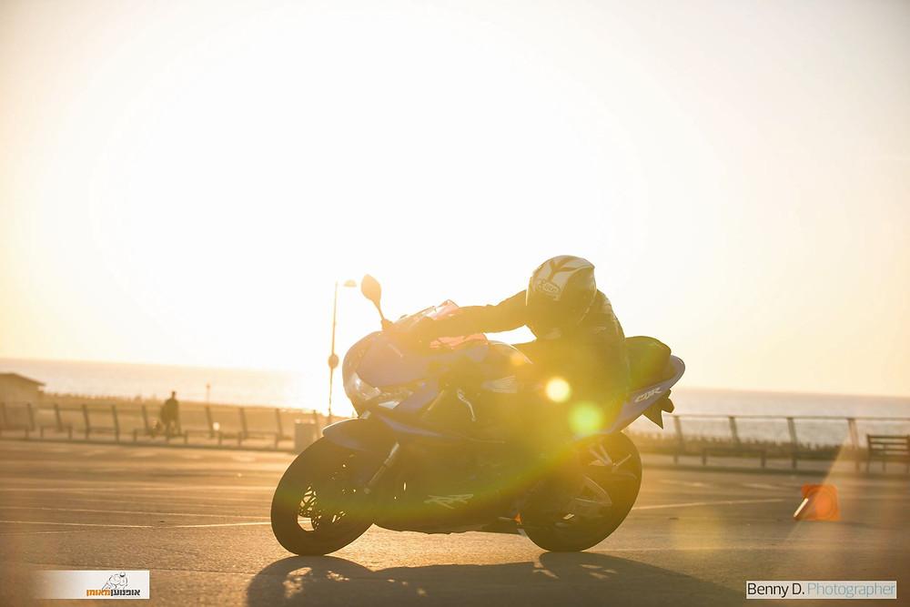 אופנוען מאומן, אופנוע ספורט במגרש, קונוס על אספלט, סינוור של שמש, צלם בני דויטש