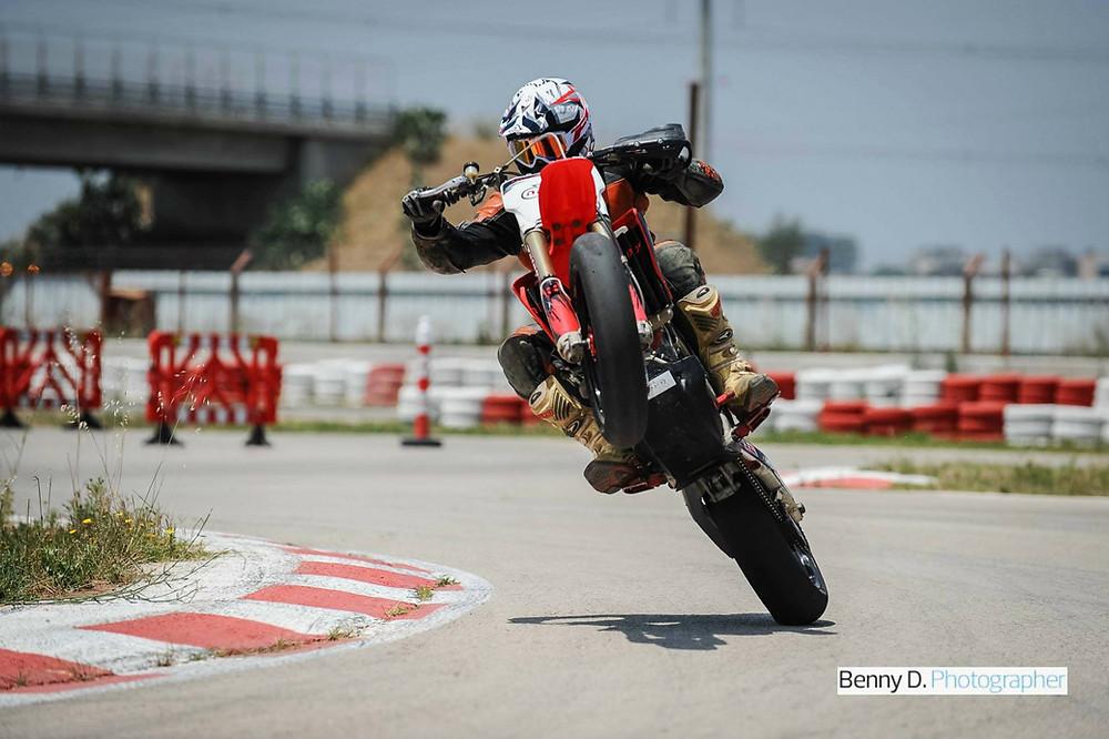 אופנוע בווילי בהטיה במסלול, שוליים צבועים באדום לבן