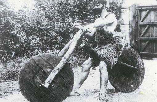 תמונת שחור לבן, איש פרימיטיבי מעידן האבן על דמוי אופנוע מעעץ.