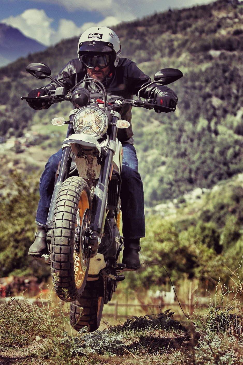 אופנוע דוקאטי סקרמבלר קופץ בשטח, רוכבעם קסדת חצי לבנה, רקע הרים
