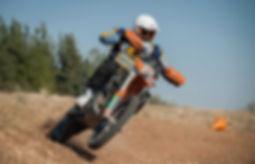 אופנוע כתום בווילי בשטח בהטיה